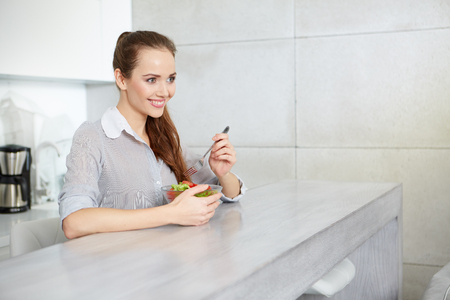 young woman smiling: young woman eating fresh salad in modern kitchen