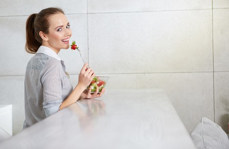 gleeful: young woman eating fresh salad in modern kitchen