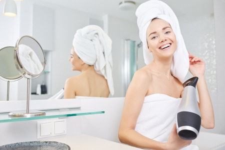 blow dry: Young girl blow drying hair in bathroom Stock Photo