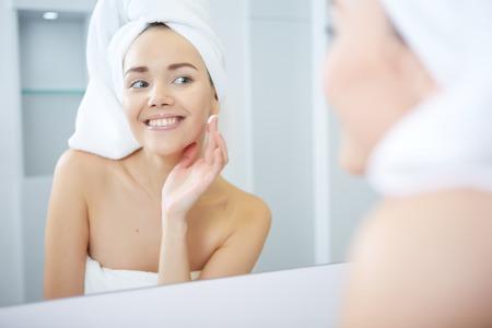 Woman applying facial moisturizing cream. Standard-Bild