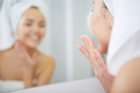 bathroom woman: Woman applying facial moisturizing cream. Stock Photo