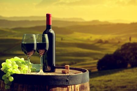 Botella de vino rojo y el vidrio en barril viejo. Toscana fondo