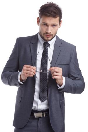 volto uomo: Bel giovane in abito grigio e occhiali sorridente isolato su sfondo bianco