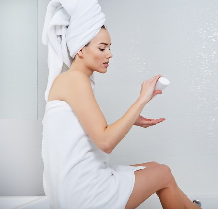 woman in bath: Attractive Young Woman Wrapped with Bath Towels, Applying Cream on her Face After a Shower at the Bathroom.