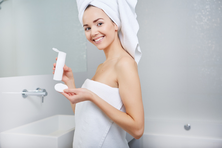 Caucasian woman: Attractive Young Woman Wrapped with Bath Towels, Applying Cream on her Face After a Shower at the Bathroom.
