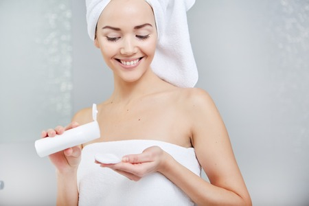 after bath: Attractive Young Woman Wrapped with Bath Towels, Applying Cream on her Face After a Shower at the Bathroom.