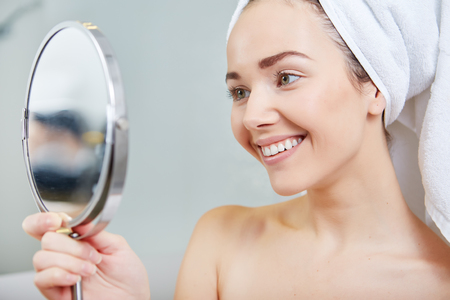 mirror face: face of young beautiful healthy woman and reflection in the mirror Stock Photo