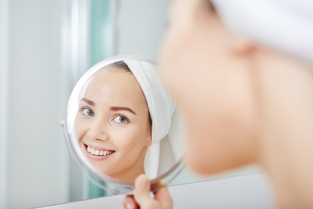 bathroom mirror: face of young beautiful healthy woman and reflection in the mirror Stock Photo