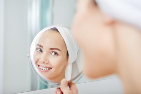 Gesicht der jungen schönen gesunden Frau und Reflexion im Spiegel