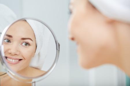 gezicht van jonge mooie gezonde vrouw en reflectie in de spiegel