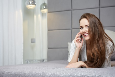 18 19: Relaxed woman at home reading a text message in her bright bedroom Stock Photo