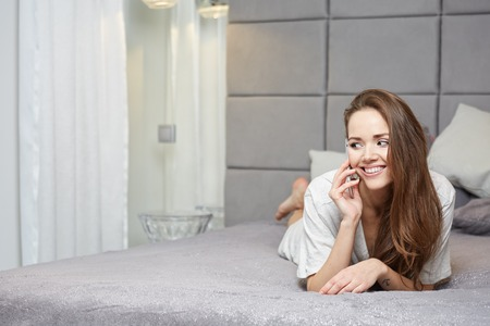 18 19 years: Relaxed woman at home reading a text message in her bright bedroom Stock Photo