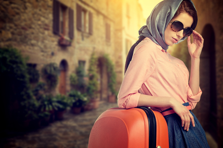 vintage travel: Elegant woman with a orange suitcase travel on street of italian city