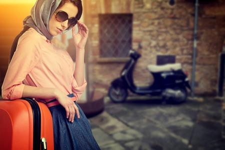 Elegante vrouw met een oranje koffer reizen op straat van de Italiaanse stad Stockfoto