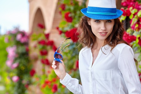 Smiling summer woman with hat and sunglasses . Italian garden