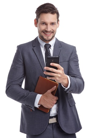career young: busy businessman with phone and folders isolated Stock Photo