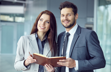 half dressed: Portrait of a smiling young business couple standing with arms crossed in a  office Stock Photo