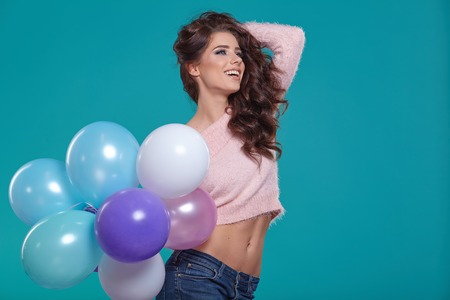 Young pretty woman with colored balloons, turquoise background 스톡 콘텐츠