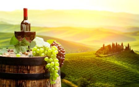 Rode wijn met vat op wijngaard in groene Toscane, Italië
