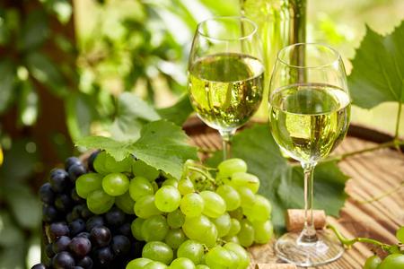 Druiven en witte wijn op houten vat op terras in de tuin Stockfoto