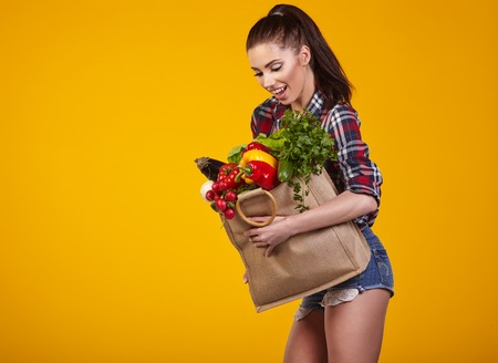 fruit market: Young woman with a grocery shopping bag. Isolated on yellow background.