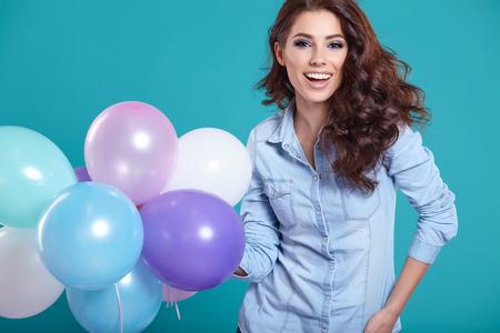 mujer alegre: Mujer joven feliz que se coloca sobre la pared azul y globos que llevan a cabo. Placer. Sueños. Virada.