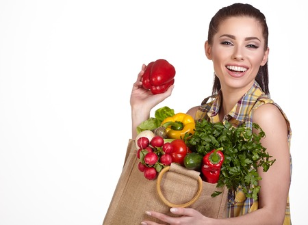 delicatessen: Woman holding a shopping bag full of fresh food, Isolated studio shoot