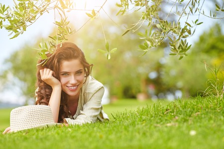 absolutely: Beautiful smiling woman lying on a grass outdoor. She is absolutely happy.