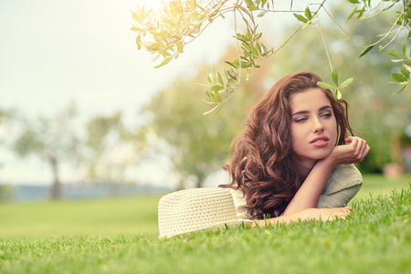 Caucasian woman: Beautiful smiling woman lying on a grass outdoor. She is absolutely happy.