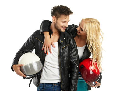man style: motorcyclists couple with helmets in hand. Studio shoot