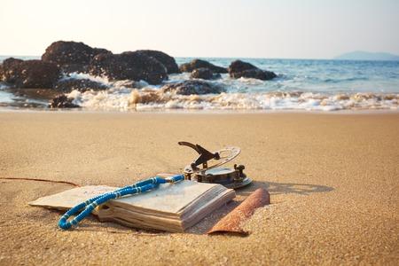 reloj de sol: Panorama de la playa tropical con el reloj de sol de época antigua y cuaderno