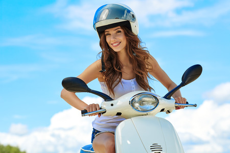 Young beautiful sexy woman sitting on a scooter outdoor