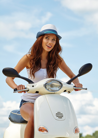 travel woman: Young beautiful sexy woman sitting on a scooter outdoor