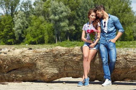 enamorados besandose: Un hombre da flores hermosa mujer. En el fondo del río y scooters