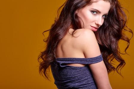 femme brune sexy: portrait d'une belle jeune fille surprise en chemise sur un fond de mur d'orange