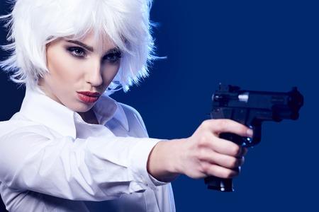 cabeza: muchacha atractiva hermosa que sostiene el arma. fondo azul Foto de archivo