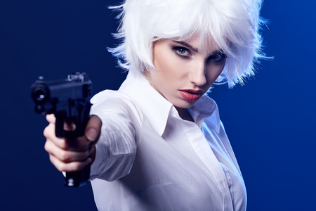 beautiful sexy girl holding gun . blue background Stock Photo