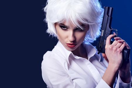 pistola: muchacha atractiva hermosa que sostiene el arma. fondo azul Foto de archivo