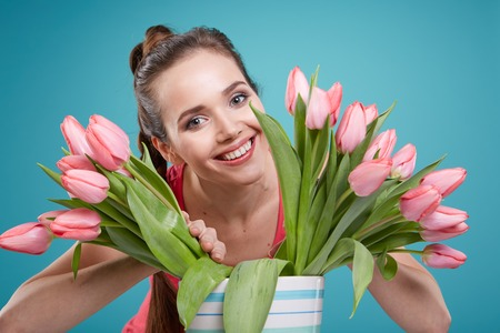 one person only: Young beautiful woman studio portrait with tulip flowers Stock Photo