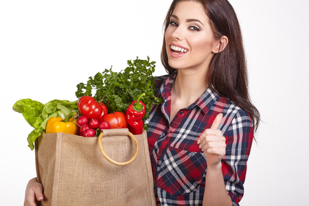 grocery baskets: Young woman with a grocery shopping bag. Isolated on white background.