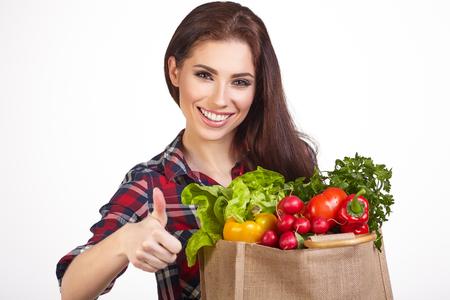 abarrotes: Mujer joven con una bolsa de compras. Aislado en el fondo blanco. Foto de archivo