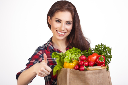 purchases: Young woman with a grocery shopping bag. Isolated on white background.