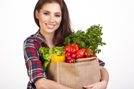 fruits in a basket: Young woman with a grocery shopping bag. Isolated on white background.
