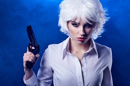 Belle fille sexy exploitation gun. arrière-plan de fumée  Banque d'images - 52487543