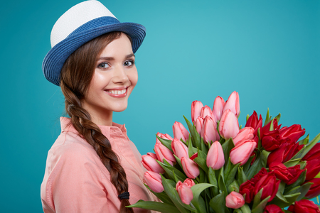 young beautiful woman: Young beautiful woman studio portrait with tulip flowers Stock Photo