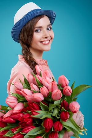 Young beautiful woman studio portrait with tulip flowers Stock Photo