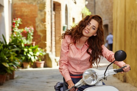 old motorcycle: Italian woman on a scooter on the streets of the Tuscan town. Stock Photo