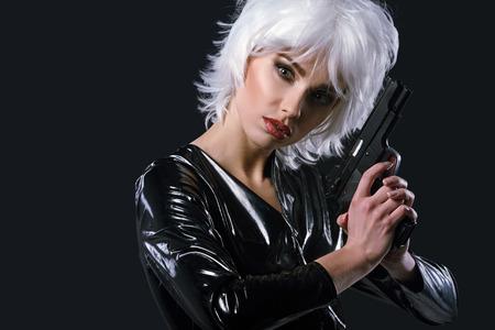 armed: beautiful sexy girl holding gun . smoke background