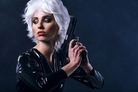 beautiful girl holding gun . smoke background Stock Photo