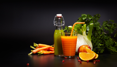 cleanse: Bottles and Glasses with fresh organic vegetable and fruit juices isolated on black. Detox diet.